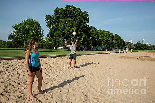 Herronstock Prints - A young couple enjoy in summer vacation playing volleyball at Zilker Park sand volleyball courts in Austin Texas