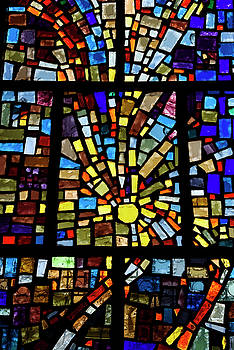 Abstract sun pattern of colors in a stained glass window mosaic  by Reimar Gaertner