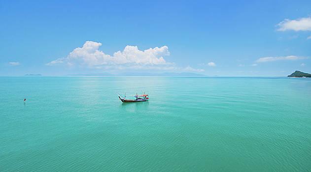 Aerial panoramic view of fishing boat on emerald sea by Lukasz Szczepanski