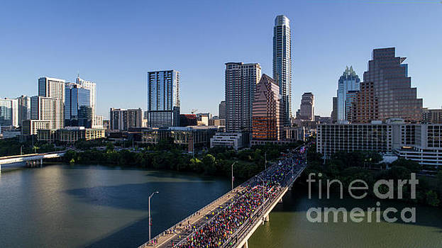 Herronstock Prints - Aerial view as thousands of runners take start the race on the Congress Avenue Bridge during the Statesman Cap10K in downtown Austin Texas