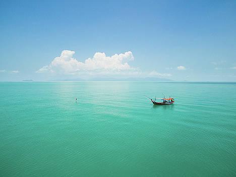 Aerial view of fishing boat on emerald sea by Lukasz Szczepanski