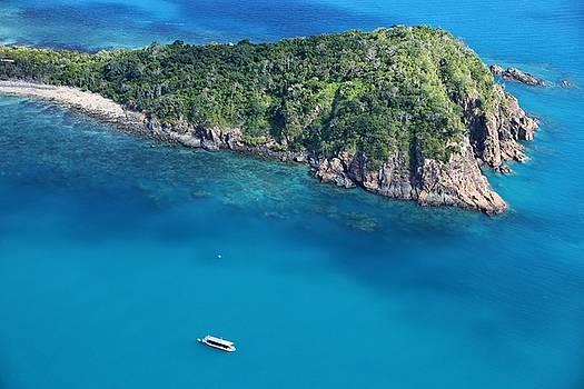 Aerial view of island and boat in The Whitsundays by Keiran Lusk