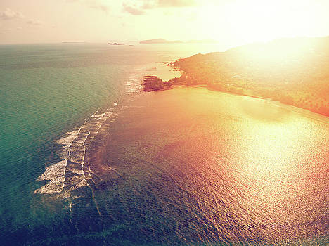 Aerial view of sunset over emerald tropical sea by Lukasz Szczepanski