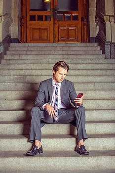 Alexander Image - American Businessman texting on cell phone, sitting on stairs