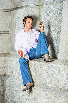 Alexander Image - American Man reading book, texting on cell phone outside.