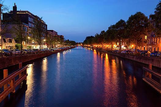Amsterdam, Netherlands- Nighttime lights over the canal by Alfio Finocchiaro