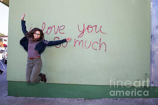 Herronstock Prints - An attractive Austin local jumps with joy in front of the iconic I Love You So Much Mural in SoCo