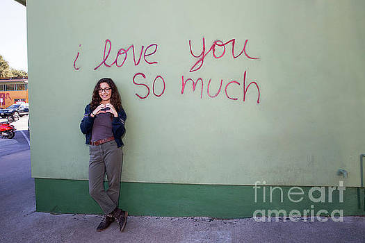 Herronstock Prints - An attractive local Austin female makes a heart  in front of the iconic I Love You So Much Mural