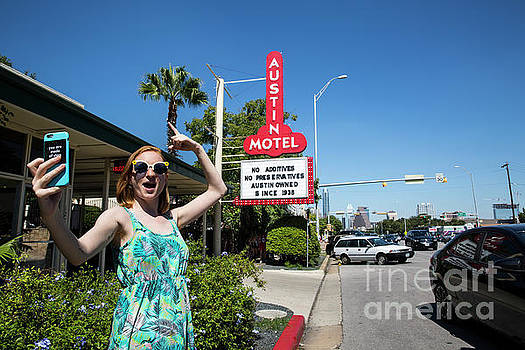 Herronstock Prints - An Austin local takes a selfie in front of the famous Austin Motel Sign in South Congress, Austins most eclectic and most popular spots for live music, dining, and unique shopping