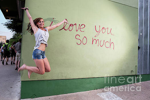 Herronstock Prints - An Austin local woman jumps for joy at the i love you so much mural on South Congress Avenue