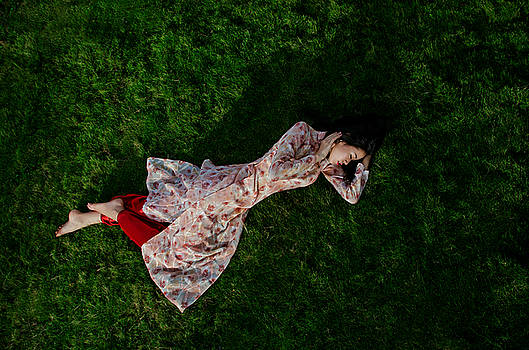 Ao dai lying on the grass by Tran Minh Quan