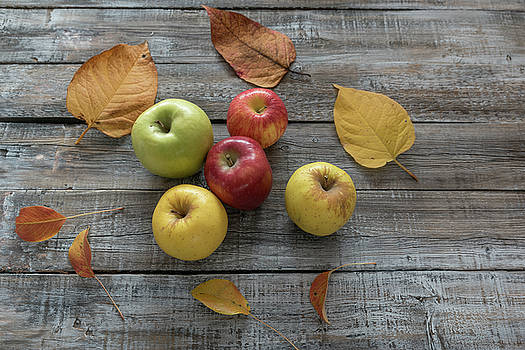 Apples and leaves on wooden boards background. Autumn concept by Julian Popov