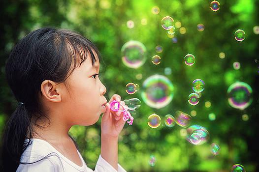 Asian kid play a bubble  by Anek Suwannaphoom