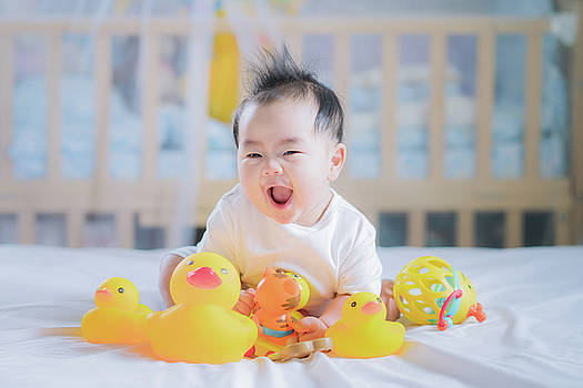 Asian New born baby sit and play an animal toy by Anek Suwannaphoom