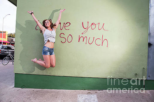 Herronstock Prints - Attractive Austin local woman jumps for joy at the i love you so much mural