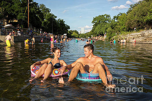 Herronstock Prints - Attractive smiling couple floating on inner tube at Barton Sprin