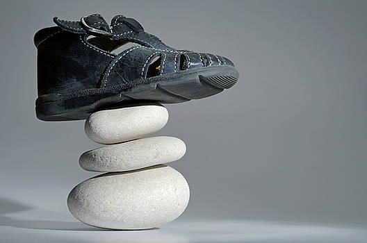 Sami Sarkis - Baby shoe on stack of pebbles