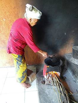 Balinese lady roasting coffee over the fire by Exploramum Exploramum