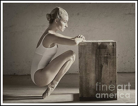 Ballerina in pointe shoes stretching by Michael Edwards