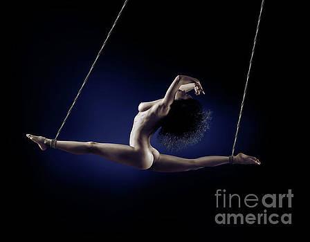 Beautiful nude woman flying suspended in splits by her ankles wi by Oleksiy Maksymenko