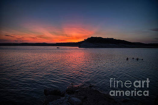 Herronstock Prints - Beautiful sunset overlooking Lake Travis as a group of swimmers enjoy the calm summer waters