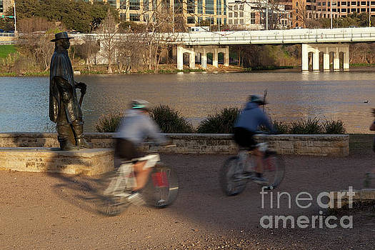 Herronstock Prints - Bike riders zoom up and down the Lady Bird Lake hike and bike trail past the Stevie Ray Vaughan Memorial Statue