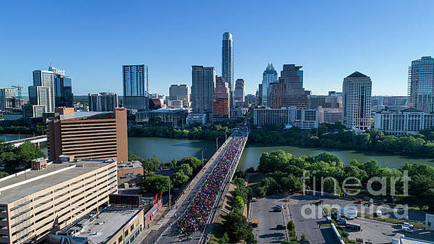 Herronstock Prints - Birds eye aerial view as thousands of runners fill up the Congress Avenue Bridge during the Statesman Cap10K in downtown Austin Texas