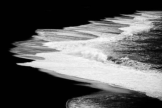 Black beach and the water of the ocean by Matthias Hauser