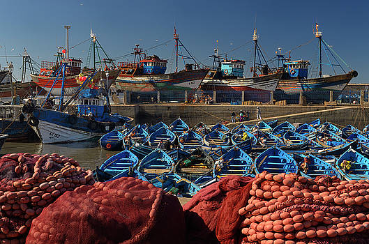 Reimar Gaertner - Blue fishing boats and red nets in the morning at the marine por