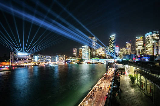 Blue Lasers cross the sky at Vivid Sydney at night by Daniela Constantinescu