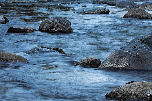 Blue waters around rocks, with reflections from the sky by Natalie Schorr