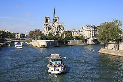 Boat cruising on the Seine River near Notre Dame by Virginie Blanquart