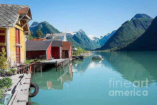 Boathouse with mountains and reflection in the fjord in Norway by IPics Photography
