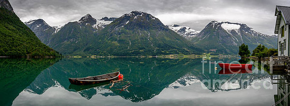 Boats and mountain reflection in the water in panorama by IPics Photography