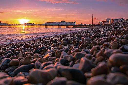 Brighton pebble beach at sunset by Marius Comanescu