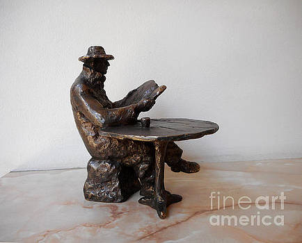 Bronze statue of Man reading a newspaper by Nikola Litchkov