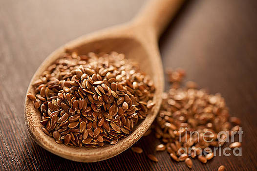 Brown flax seeds heap by Arletta Cwalina