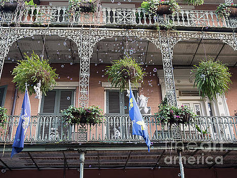 Bubbles blow from an ornate balcony in New Orleans at Mardi Gras by Louise Heusinkveld