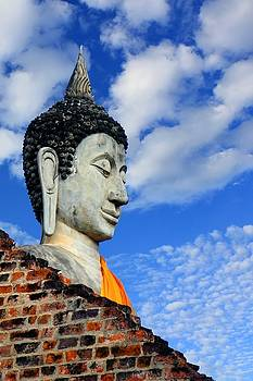 Buddha head shot with blue sky by Chaitawat Pawapoowadon