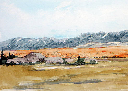 Buildings on a Colorado ranch with mountain landscape by R Kyllo