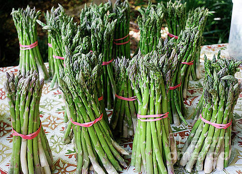 Bundles of asparagus on display at a farmers market by Louise Heusinkveld