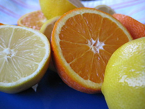 Citrus on blue plate by Kim Pascu