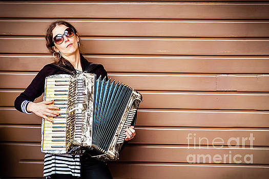 Closed shutter serenade - woman play accordion by Luca Lorenzelli