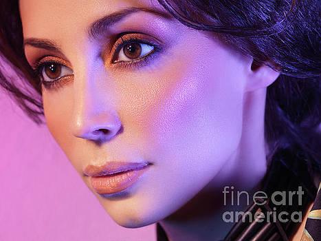 Closeup beauty portrait of woman face in colored purple light by Oleksiy Maksymenko
