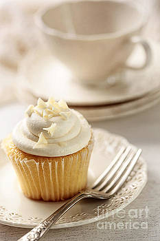 Sandra Cunningham - Closeup of vanilla cupcake with tea cup