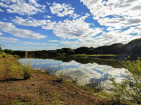 Clouds reflecting on the Uruguay river by Helissa Grundemann