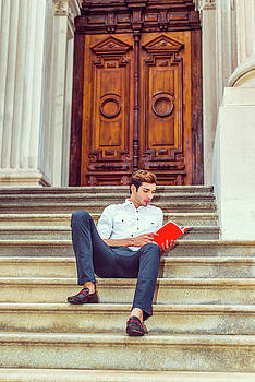Alexander Image - College student reading red book, sitting on stairs, relaxing ou