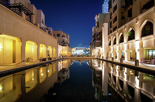 Colorful reflection of souk building in Downtown area during calm night. Dubai, United Arab Emirates. by Marek Kijevsky