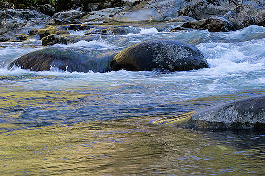 Colorful reflections of fall leaf colors and sky on river water with rocks by Natalie Schorr