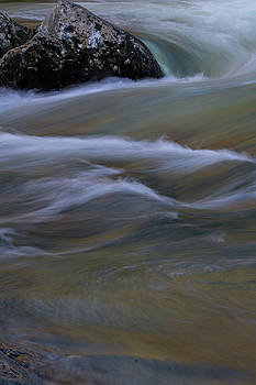 Colorful river water currents swirling around a rock by Natalie Schorr